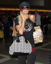 Paris wore a casual newsboy cap for her flight at LAX.