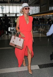 Paris Hilton topped off her airport look with a printed tote from her own line.