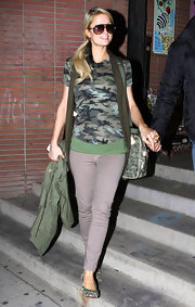 Paris Hilton stays casual in a pair of bow embellished gray flats. She paired the shoes with a camouflage tee.