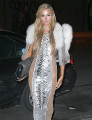 Paris Hilton stepped out in New York City sporting a statement-making snakeskin clutch (from her own line), sheer-panel gown, and fur vest combo.