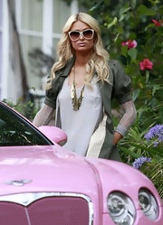 Paris Hilton was seen getting into her pink Bentley wearing a gilded gold chain necklace. The perfect match for her army green jacket.