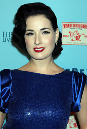 Dita Von Teese always steps out looking elegant. The dancing diva spiced up her look with retro Marcel waves and a swipe of vivid red lipstick.