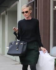 Portia layered this textured black sweater for a chic dark shopping look.