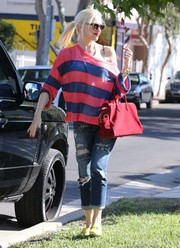 Gwen Stefani went for bold colors, complementing her striped top with a bright red suede tote.