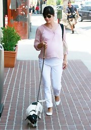 Selma walks her dog in slim fitting white maternity jeans and a pink tunic.