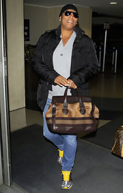 Queen Latifah traveled in comfort in a pair of gray sneakers with bright yellow laces.