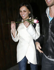Rachael looks classic in a white wool coat, holding a pink rose.