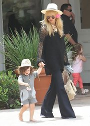 Flare jeans, a loose weave top, and a wide-brimmed straw hat topped off Rachel's signature hippie look.