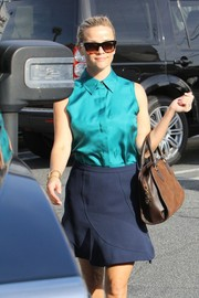 Reese Witherspoon looked effortlessly stylish in her navy mini skirt and green top combo.
