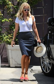 For a chicer finish, Reese Witherspoon teamed her tee with a navy pin-dot pencil skirt by Draper James.