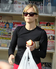 Reese Witherspoon stocked up on magazines in workout gear and a pair of black wayfarer style sunglasses.
