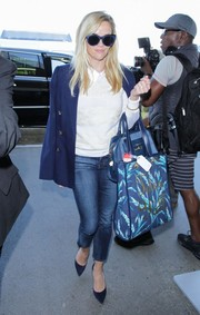 Reese Witherspoon caught a flight out of LAX looking preppy in a collared, lace-striped sweater by Draper James.
