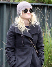 Reese wears a gray knit beanie with her aviator sunglasses.