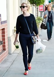 Reese Witherspoon added a pop of color to her outfit with bright red ballet flats.