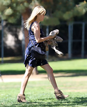 Reese accessorized her look with brown suede ankle boots.