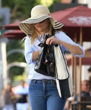 Reese Witherspoon ran errands on a sunny day wearing a floppy straw hat.