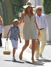 Penny Lancaster teamed up her sun dress with a chic hat at an Easter party.