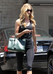 Rosie Huntington-Whiteley styled her gym get-up with a green leather tote by Saint Laurent.