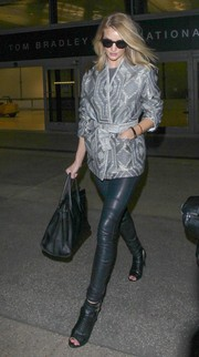 Rosie Huntington-Whiteley touched down at LAX looking oh-so-chic in a silver kimono jacket by IRO teamed with black leather leggings.