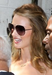 Rosie Huntington-Whiteley charmed in a pair of gold aviator sunglasses with rosy lenses.