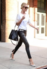 Rosie Huntington-Whiteley amped up the tough-chic vibe with a studded black bucket bag by Saint Laurent.