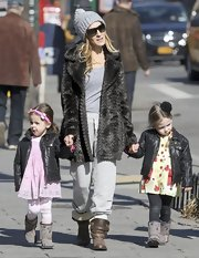 Sarah Jessica Parker donned a gray fur coat over some sweat pants for a quick walk through NYC with her daughters.