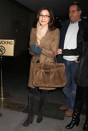 Michelle Yeoh bundled up in a classic light brown wool coat with silver button details on its pockets.