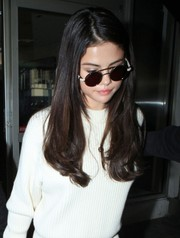 Selena Gomez kept a low profile with a pair of round shades as she made her way through LAX.