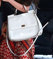 Selena sported a white patent leather tote while out at the salon.