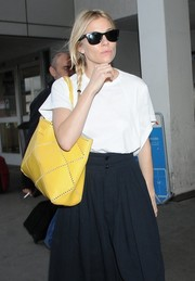 Sienna Miller touched down at LAX wearing classic wayfarer sunglasses.
