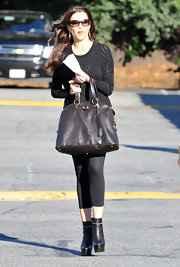 Sofia Vergara dressed up a pair of black leggings with a pair of chain trimmed black leather ankle boots. The boots gave Sophia a major boost thanks to sky high platforms.