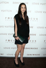 China Chow added a pop to her all black look with a forest green snakeskin clutch.