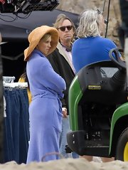 Katie wears a big brimmed sunhat on the set of Melrose Place.