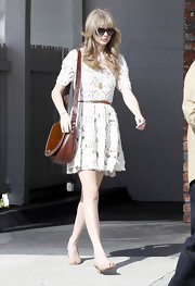 T. Swizzle topped off her lacy frock with nude peep-toe kitten heels.
