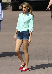 Taylor Swift paired denim shorts with a classic blouse for a casual but stylish look.