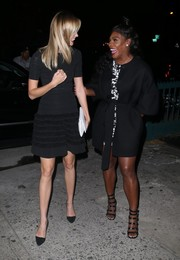 Serena Williams layered an elegant black coat over a printed mini dress for a night out with her friends.