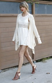Taylor Swift layered a white sharkbite-hem cardigan (also by Free People) over her mini for added pizzazz.