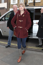 Taylor Swift maintained her classic approach to street style with a maroon toggle coat and leather accessories.