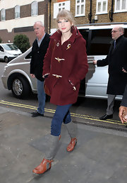 Taylor Swift opted for comfy style while out and about London. She paired her burgundy coat with flat riding-style boots.