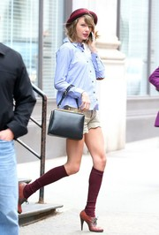 Taylor Swift complemented her button-down with cute scalloped-hem beige shorts.