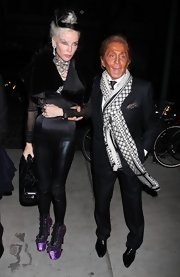 Daphne Guinness wore statement making Nina Ricci ankle boots. The vibrant purple boots feature imposing platforms and crystal embellishments.