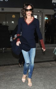 Victoria Beckham was relaxed yet stylish in a blue and red V-neck sweater from her own label while arriving on a flight at LAX.