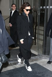Victoria Beckham traded in her usual high-heeled footwear for more comfy Adidas sneakers.