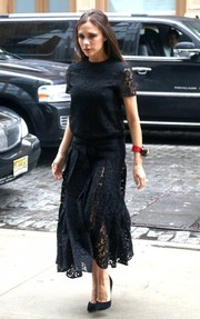Victoria Beckham cut an elegant figure on the streets of New York City in a little black lace dress from her own label.