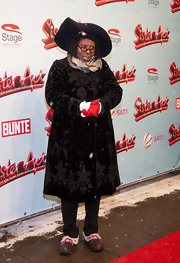 Whoopi loves to make a statement on the red carpet. Here she dons a velvet embroidered coat with a large hat and slippers!