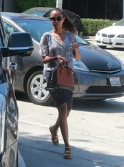 Zoe Saldana accessorized with a stylish red and black bowler bag.