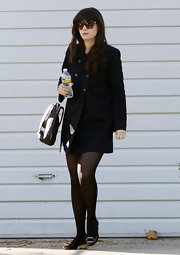 Zooey Deschanel covered up in a classic navy wool coat and buckled kitten heels.