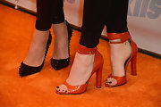 Kylie added some color to her all-black look with this pair of orange ankle-strap sandals.