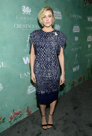 Greta Gerwig kept it ladylike in a navy Oscar de la Renta midi dress featuring a warped lattice print and puffed sleeves at the Women in Film pre-Oscar party.