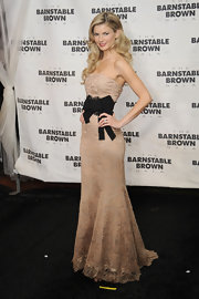 The supermodel looked statuesque in a lacy nude gown with a glamorous side-parted, wavy hairstyle.